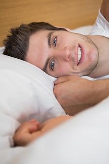 Hombre guapo sonriendo en la cama