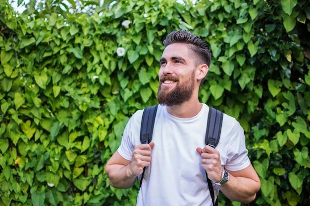 Hombre guapo sonriendo, con su mochila de aventura sobre un fondo de hojas verdes y naturales.