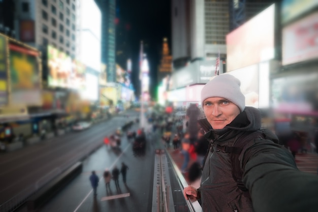 Hombre guapo sonriendo y tomando fotos selfie en times square en nueva york