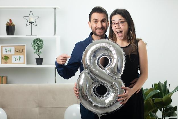 Hombre guapo sonriente apuntando a una mujer joven y bonita sorprendida con gafas sosteniendo un globo en forma de ocho de pie en la sala de estar en el día internacional de la mujer de marzo