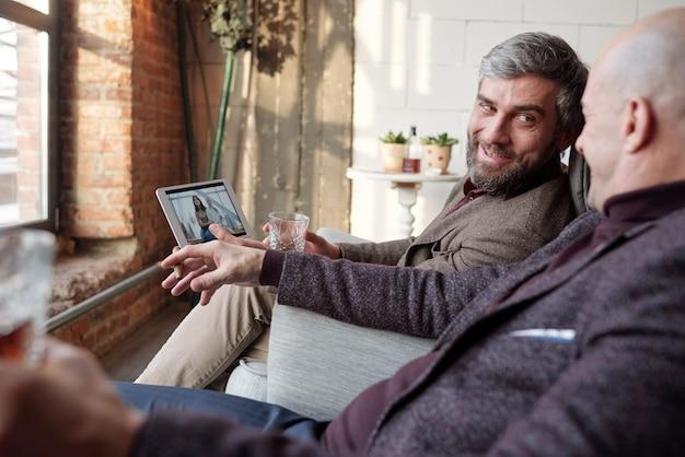 Hombre guapo sonriente con barba sentado en un sillón y sosteniendo la tableta con una foto de familia en la pantalla mientras habla con un amigo