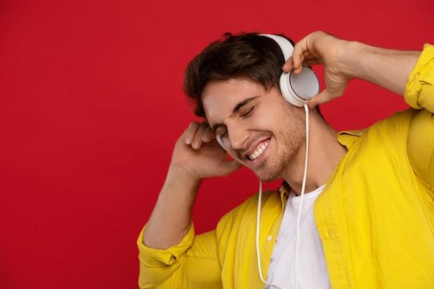 Hombre guapo sonriente en camisa amarilla escuchando música en auriculares con los ojos cerrados, aislado en rojo
