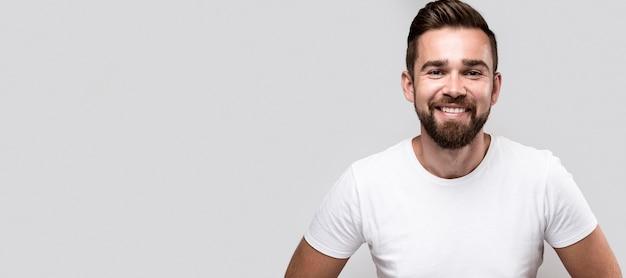 Hombre guapo sonriente en camiseta blanca con espacio de copia