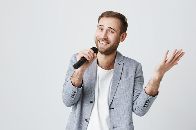 Hombre guapo sonriente cantando karaoke con micrófono