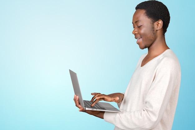 Hombre guapo sonriente feliz con laptop