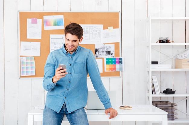 Hombre guapo sonriente sentado en la oficina y escribiendo un mensaje en el teléfono móvil