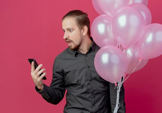 Hombre guapo sorprendido se encuentra con globos de helio mirando teléfono aislado