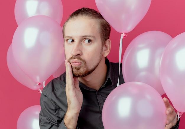 Hombre guapo sorprendido se encuentra con globos de helio pone la mano en la cara mirando al lado aislado