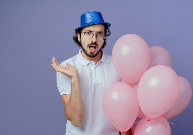 Hombre guapo sorprendido con gafas y sombrero azul sosteniendo globos y extendiendo la mano aislada sobre fondo púrpura