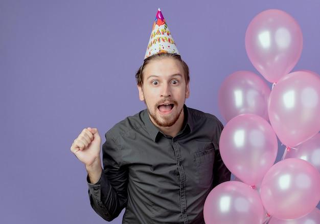 Hombre guapo sorprendido con gorra de cumpleaños sostiene globos de helio y mantiene el puño en alto aislado en la pared púrpura