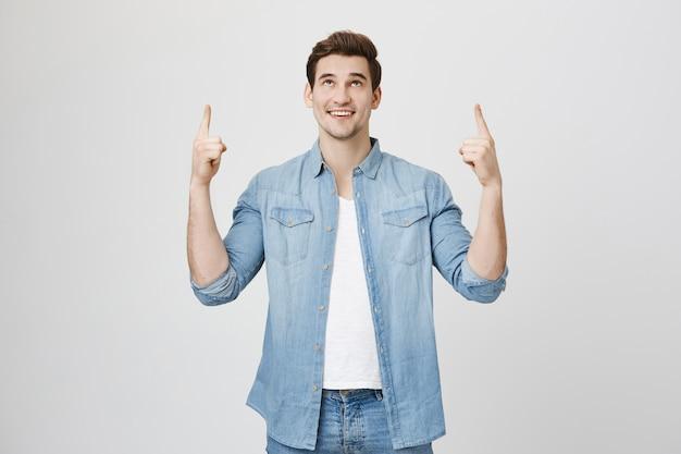 Hombre guapo sorprendido mostrando pancarta, apuntando hacia arriba