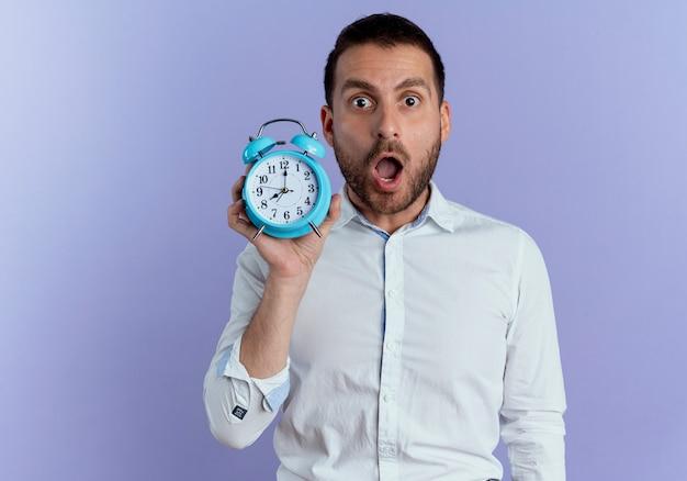 Hombre guapo sorprendido tiene reloj despertador aislado en la pared púrpura