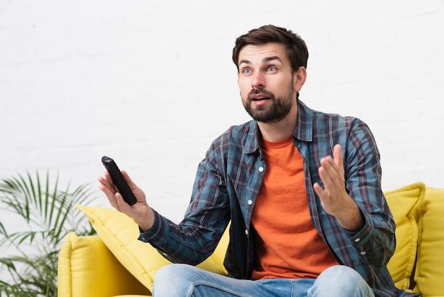 Hombre guapo sorprendido viendo tv