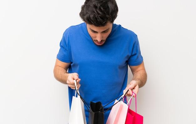 Hombre guapo sosteniendo un montón de bolsas de compras