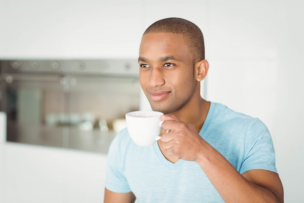 Hombre guapo sosteniendo la taza en la cocina