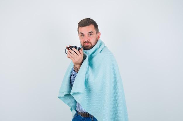 Hombre guapo sosteniendo una taza de té con ambas manos en camisa, jeans, chal y mirando agotado. vista frontal.