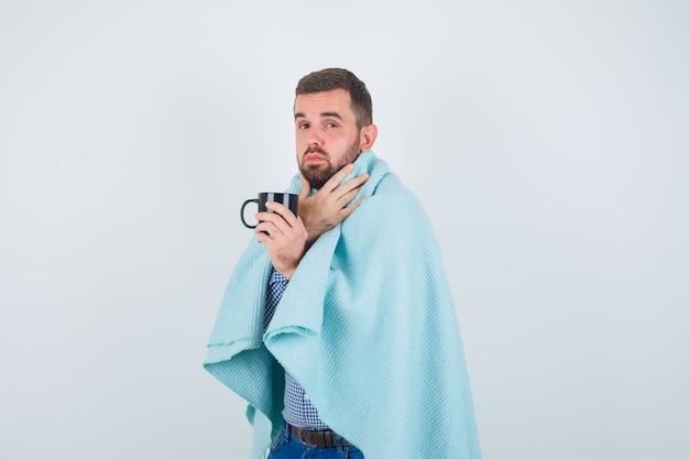 Hombre guapo sosteniendo una taza de té, con dolor de garganta en camisa, jeans, chal y mirando exhausto, vista frontal.