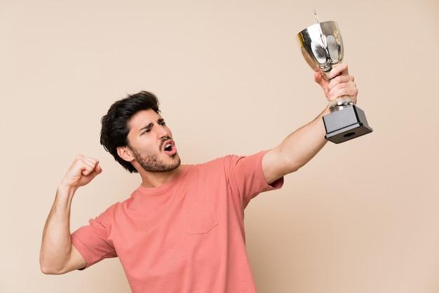 Hombre guapo sosteniendo un trofeo