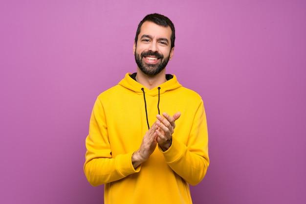 Hombre guapo con sudadera amarilla aplaudiendo después de la presentación en una conferencia