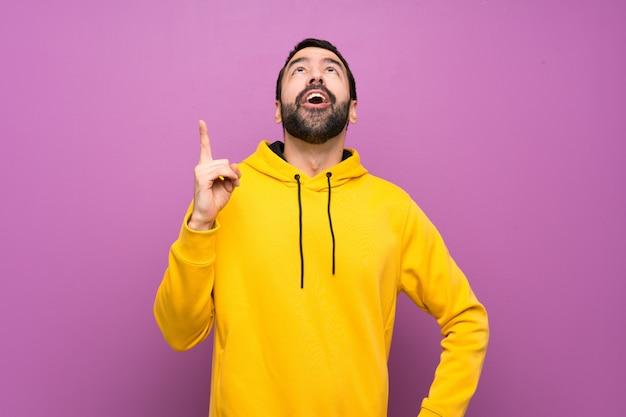Hombre guapo con sudadera amarilla apuntando hacia arriba y sorprendido.