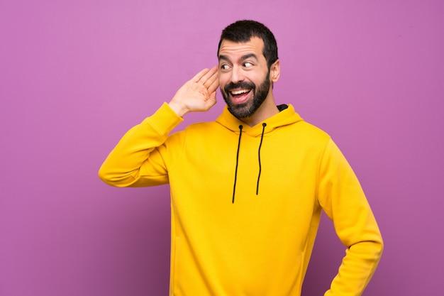 Hombre guapo con sudadera amarilla escuchando algo poniendo la mano en la oreja