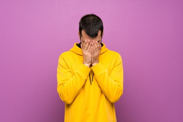 Hombre guapo con sudadera amarilla con expresión cansada y enferma