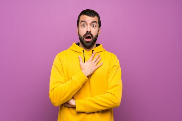 Hombre guapo con sudadera amarilla sorprendido y sorprendido mientras mira a la derecha