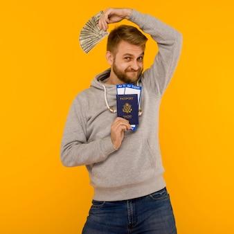 Un hombre guapo con una sudadera con capucha gris se regocija al ganar la lotería. tiene un pasaporte con billetes de avión y dinero.