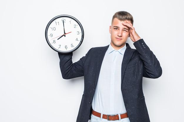 Hombre guapo en suite mantenga gran reloj en una mano aislado en blanco, concepto tardío