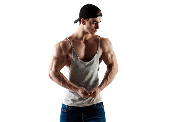 Hombre guapo súper alto musculoso en gorra de béisbol y camiseta sin mangas posando sobre fondo blanco