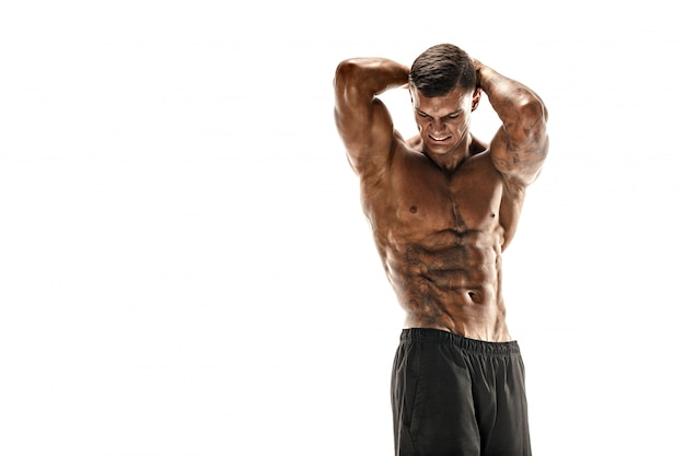 Hombre guapo súper alto musculoso posando en escena blanca