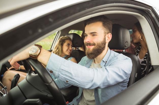 Hombre guapo con sus amigos que viajan en coche