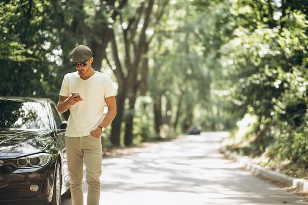 Hombre guapo con teléfono en coche