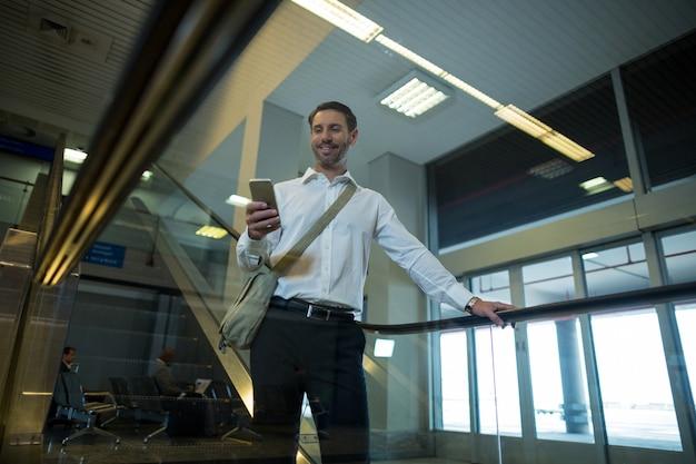 Hombre guapo con teléfono móvil en la escalera mecánica