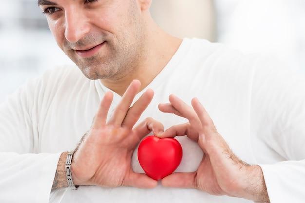 Un hombre guapo tiene un corazón rojo en la mano y sonríe feliz, aislado sobre fondo blanco