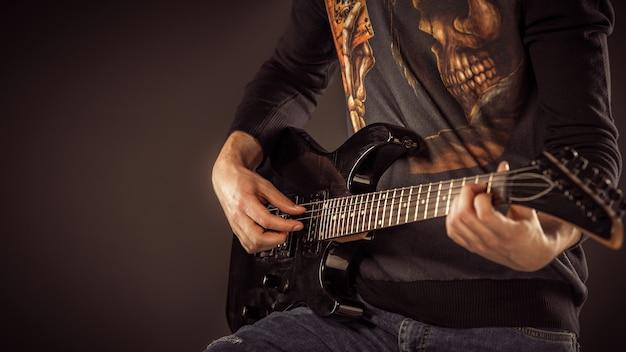 Hombre guapo tocando la guitarra electro, tiro