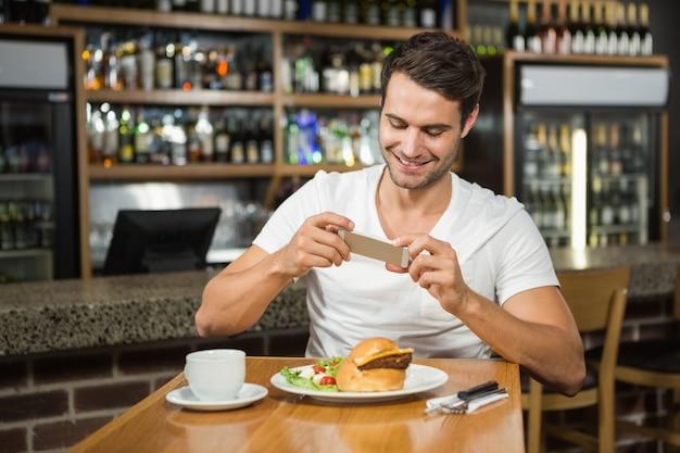 Hombre guapo tomando una foto de su comida