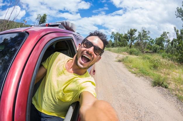 Hombre guapo tomar una selfie en un auto en el viaje