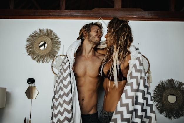 Hombre guapo con torso desnudo abraza a su novia y la cubre con una alfombra a rayas