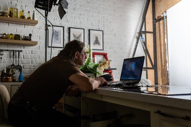 Hombre guapo está trabajando en el centro de datos con ordenador portátil.