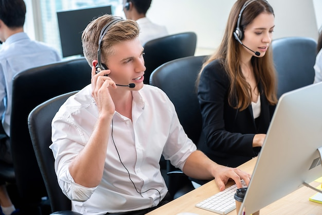 Hombre guapo trabajando como personal de atención al cliente con el equipo en el centro de llamadas