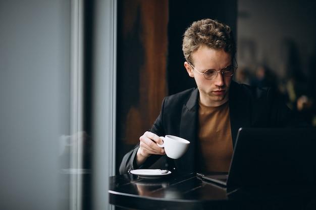 Hombre guapo trabajando en una computadora en un café y tomando café