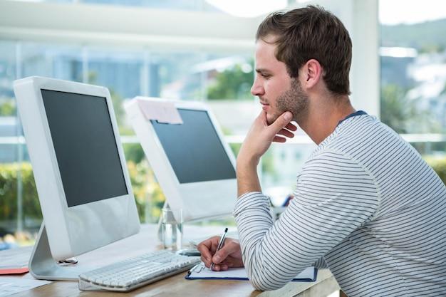 Hombre guapo trabajando en la computadora y tomando notas en una oficina brillante