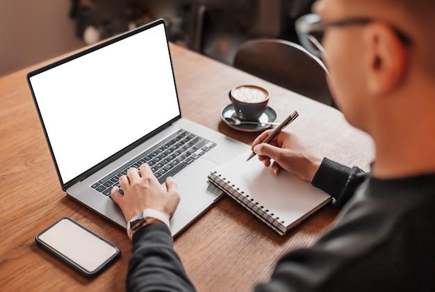 Hombre guapo trabajando en equipo portátil en el lugar de trabajo. empresario escribiendo información en la computadora en la mesa de trabajo con café, teléfono y bloc de notas