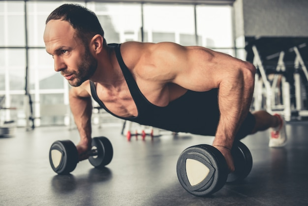 Hombre guapo está trabajando con pesas en el gimnasio.