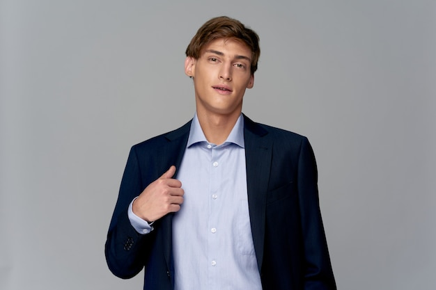 Hombre guapo en un traje clásico endereza su chaqueta