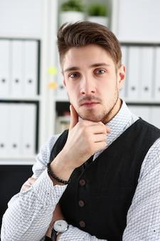 Hombre guapo en traje y corbata de pie en la oficina