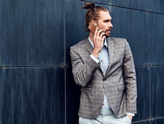 Hombre guapo en traje a cuadros gris hablando con teléfono inteligente