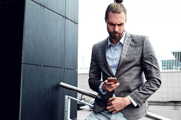 Hombre guapo en traje a cuadros gris con smartphone