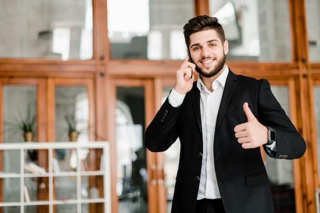 Hombre guapo en traje muestra pulgares arriba y habla por teléfono